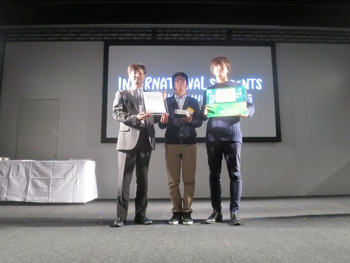 審査員である凸版印刷 重田成男様から賞状・トロフィーを授与された加藤大久さん(写真中央)、浦口昂久さん(写真右)