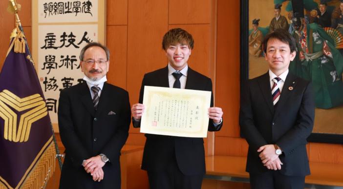写真左から国立能登青少年交流の家 佐藤博之所長、 ボランティア表彰された電気電子工学科4年の平澤実哉弥さん、大澤 敏 学長