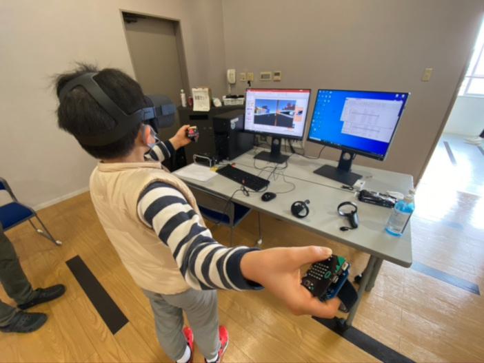 金沢工業大学オリジナルの弓による的宛てゲームを体験する児童。「弓をつがえる → 弓を放つ → 弓の強さを変える」というようにコントローラの改良を行うストーリーになっている
