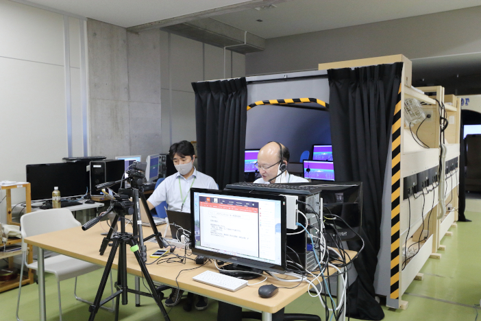 増設されたフライトシミュレータの前から橋本教授(右)と佐々木教授が講義・演習を配信
